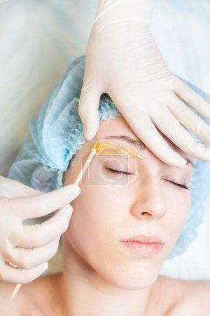 Photo pour Closeup belle femme dans le salon spa recevant l'épilation ou la correction des sourcils à l'aide de sucre - sucres. Vous pouvez voir son sourcil lisse après épilation - image libre de droit
