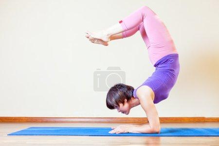 Asian woman doing exercise of yoga at mat