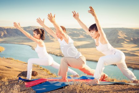 Photo pour Entraîneur asiatique conduit des cours de yoga de groupe en plein air, à la montagne. Concept d'un mode de vie sain et la bonne attitude à la vie. Chine - image libre de droit