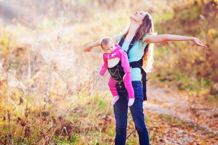 Photo pour Bonne mère portant son enfant par porte-bébé ergonomique. Ils marchent en plein air au parc national de montagne à l'automne - image libre de droit
