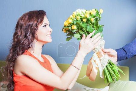 Photo pour Belle femme heureuse a reçu un bouquet de fleurs de roses chinoises. Ami a donné des fleurs. Concept de vacances, anniversaire, Journée mondiale sur les femmes ou les Valentin, 8 mars - image libre de droit