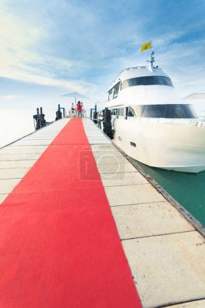 Yacht docking at the pier with red carpet to party