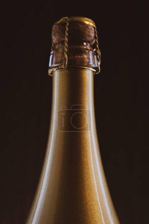 Cuello de botella de champán dorado sobre un fondo oscuro. Enfoque suave