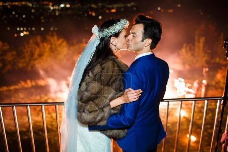 Photo pour L'heureux couple baiser est célébrer leur mariage sur le pétard de fond - image libre de droit