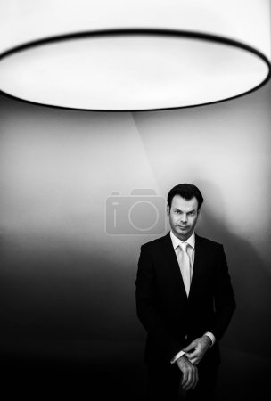 Photo for Stylish handsome businessman on the background classic hotel room  black and white - Royalty Free Image