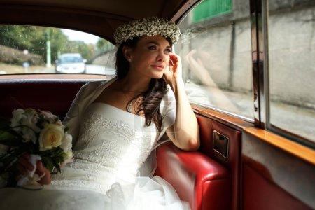 Foto de Madrina de lujo hermosa corona con ramo de orquídeas y de sutting en coche - Imagen libre de derechos