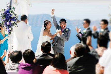 Photo pour Heureuse mariée asiatique chic et groom souriant, main dans la main - image libre de droit