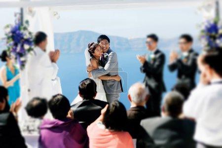 Photo pour Rich élégant souriant asiatique mariée et cérémonie de mariage de marié hugging en île de soleil de Santorin en Grèce - image libre de droit