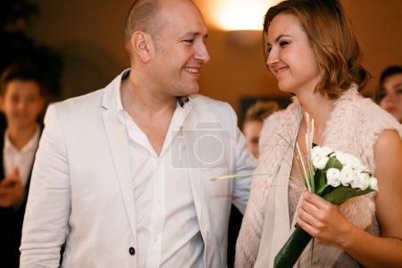 Photo pour Heureux sourire élégant riche mariée et marié regarder l'autre se marier cérémonie de mariage - image libre de droit