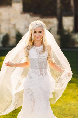 gently blonde bride in lace dress backgroung wall in garden