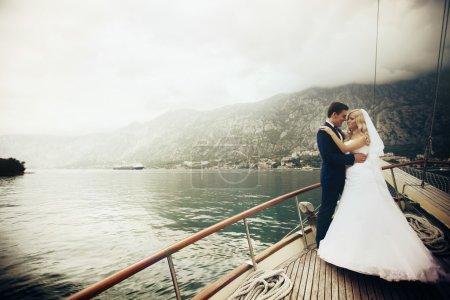 Photo pour Élégant jeune mariée et marié étreignant et embrassant à bord du yacht Monténégro - image libre de droit