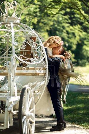 Photo pour Romantique couple de mariage de conte de fées mariée et marié baisers dans une voiture blanche de Cendrillon magique - image libre de droit