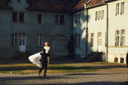 Photo pour Mariage conte de fées couple beau marié balançant belle mariée au coucher du soleil château fond - image libre de droit
