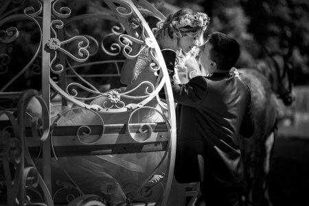 Photo pour Romantique couple de mariage de conte de fées mariée et marié étreignant dans le chariot blanc magique Cendrillon b & w - image libre de droit