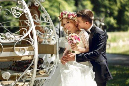Photo pour Romantique couple de mariage de conte de fées mariée et marié étreignant dans un chariot blanc de Cendrillon magique - image libre de droit
