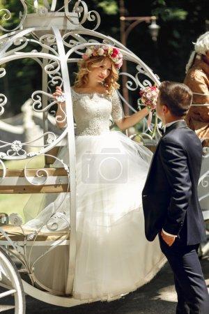 Photo pour Romantique couple de mariage de conte de fées mariée et marié posant dans une voiture blanche Cendrillon magique - image libre de droit