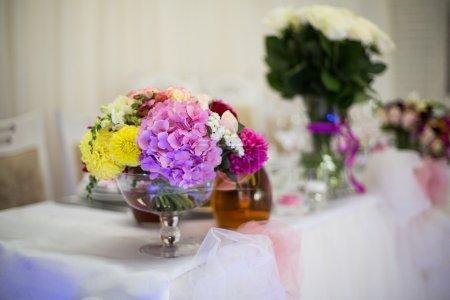 Photo pour Belles fleurs fraîchement coupées dans un vase en verre sur table de réception de mariage gros plan - image libre de droit