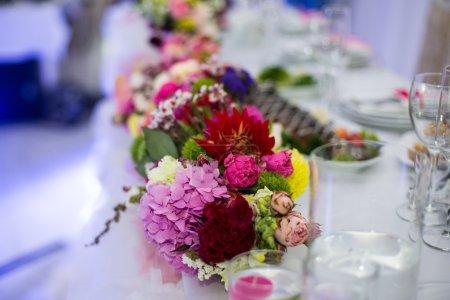 Foto de Hermosas flores recién cortadas en jarrones de vidrio en el primer plano de la mesa de recepción de la boda - Imagen libre de derechos