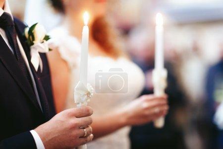 bride and elegant groom holging candles