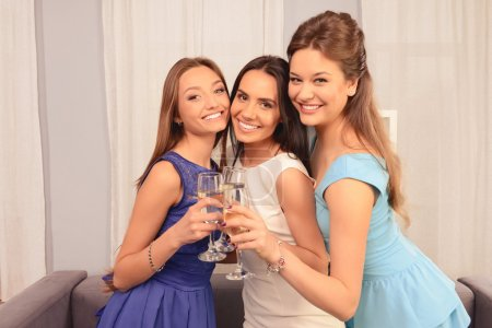 Three happy glamour girls holding glasses with shampagne and smi