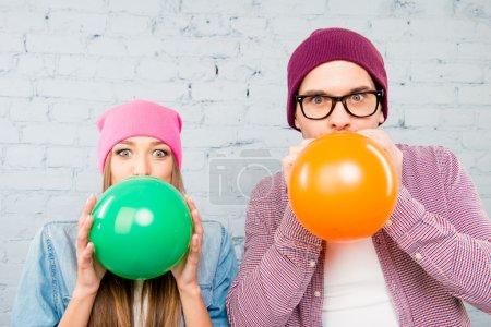 Portrait of attractive man and woman in hats inflating balloons