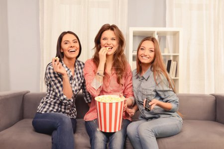 Happy smiling girls having gatherings with comedy and popcorn