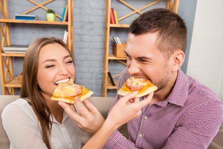 Happy cheerful man and woman feeding each other with pizza