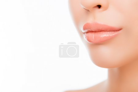 Close up photo of woman's lips with natural make up on white bac