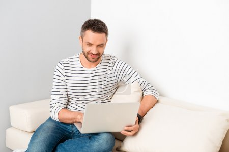 Handsome man sitting on sofa and reading news on laptop
