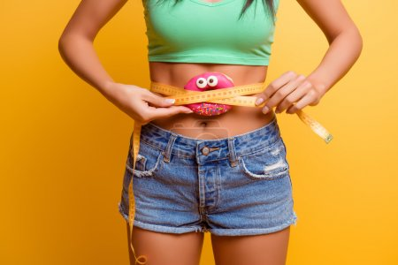 girl  holding pink donut near her belly with centimeter.  she a