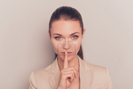 Young pretty businesswoman making silent gesture with finger on