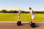 Happy young couple having date and riding segway in park