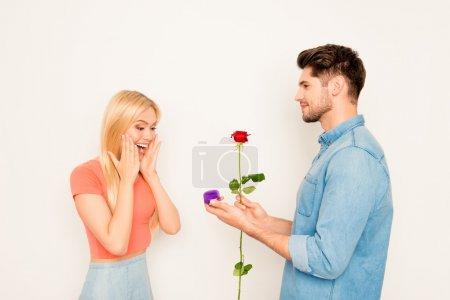 Jeune homme avec rose faisant la demande en mariage à sa petite amie