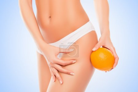 Woman in white panties holding orange near hip and checking fat