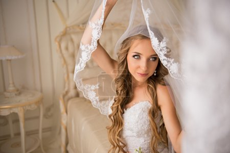 Beautiful bride in her bright bedroom sitting on a luxurious white bed and holding her beautiful long veil veil