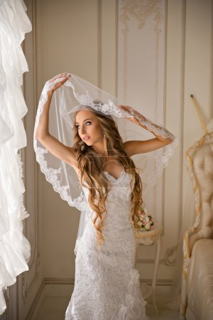 Beautiful bride in her bright bedroom near the window holding her veil
