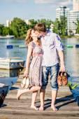 Pár v lásce sedící na dřevěném molu v blízkosti lodi. Muž a žena polibek na lavici obžalovaných