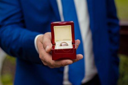 Recadrage d'image d'époux tenant une boîte avec des anneaux de mariage