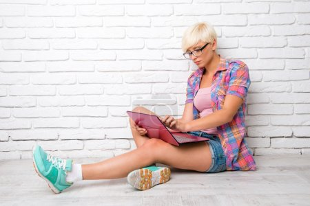 Top view of young woman siting on the floor and working at a lapt