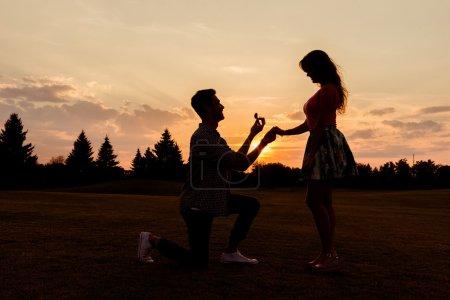 Silhouette d'un homme fait une proposition de fiançailles à sa petite amie