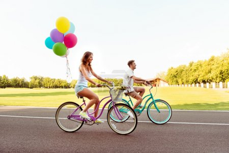 Happy smiling couple ride bicycles have fun