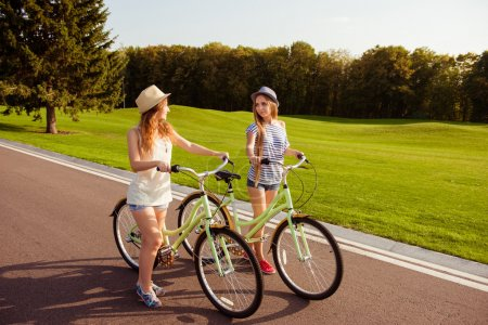 two pretty happy  girls  walking with a bicycle on park