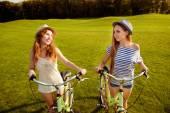Roztomilé dívky s klobouky, chůze se kolo na trávníku