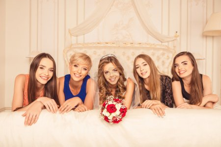 Cute bride with bridesmaids lying on the bed