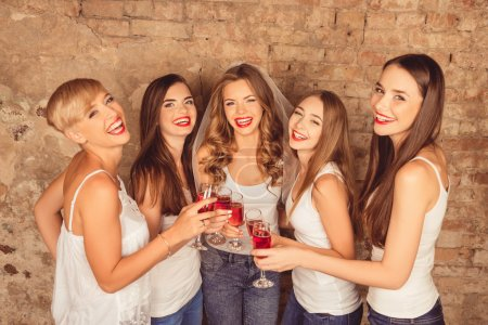 Attractive bride and happy bridesmaids celebrating hen-party wit