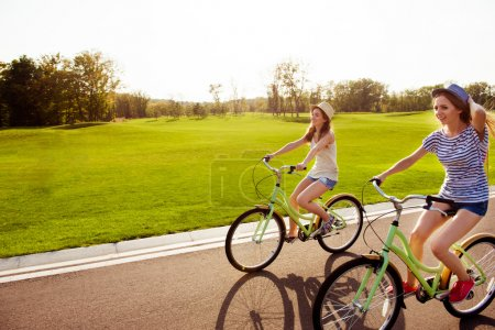 positive happy girls in love ride bicycles and have fun
