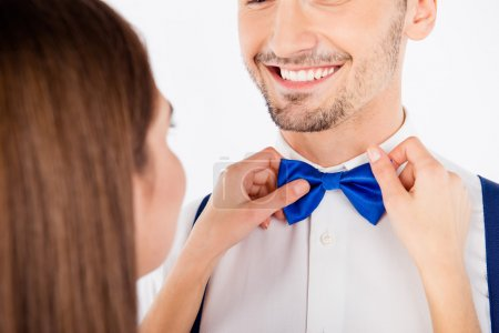 Closeup photo of a girl binding a blue bow to her boyfriend