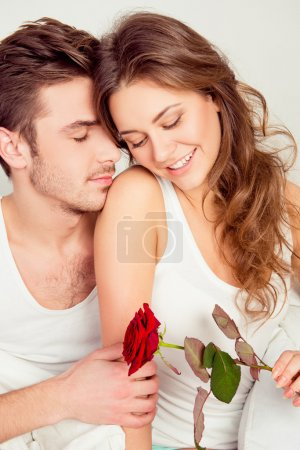 Happy cute couple in love at home embracing each other with a ro