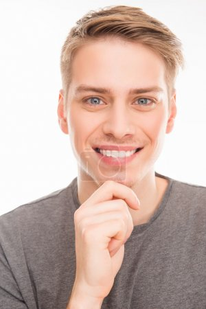 Close up photo of smiling man touching his chin