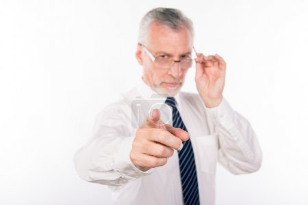 Old businessman holding his glasses and pointing at the camera